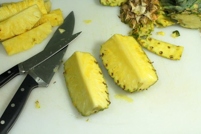 How to cut pineapple - Cut into quarters lengthwise - Real: The Kitchen and Beyond