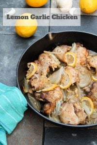 chicken thighs in cast iron pan with lemon and onion, lemon on table and blue towel around pan handle