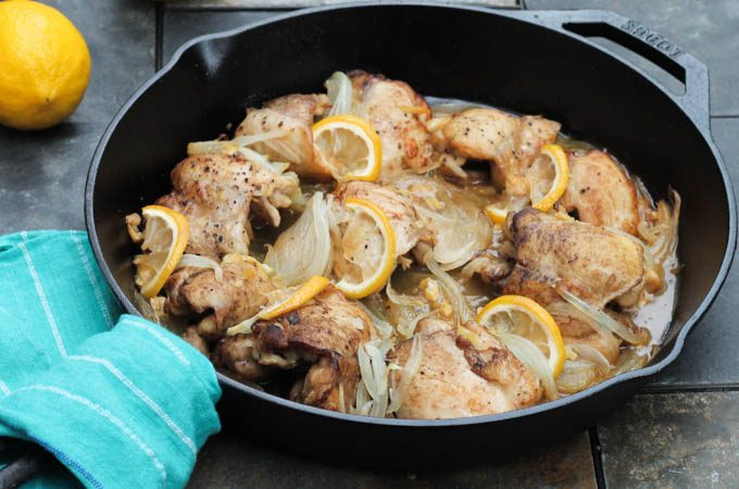 chicken thighs in cast iron pan with lemon and onion blue towel around handle of pan